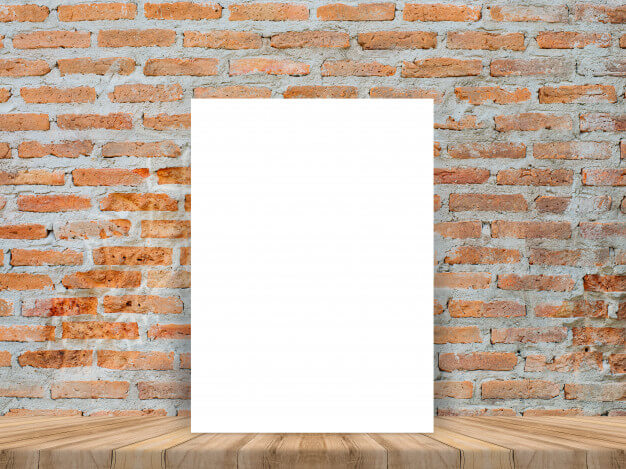 Blank white poster at wood table with brick wall