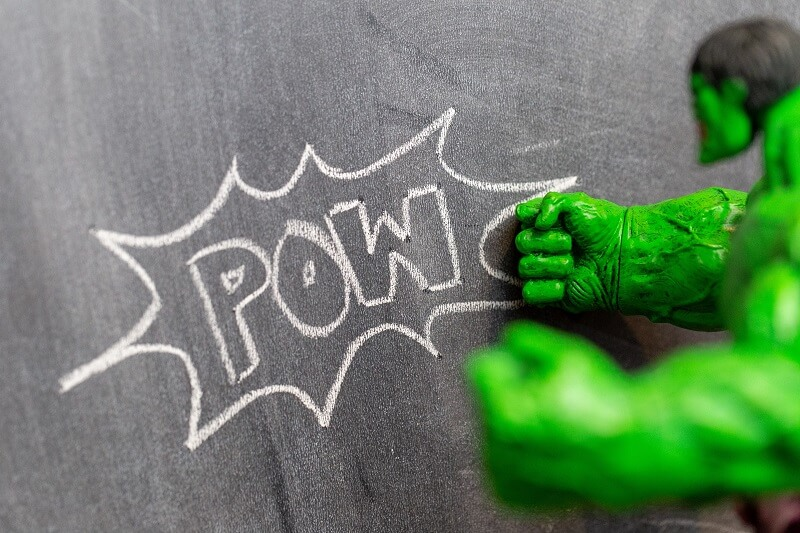Hulk toy punching a POW sign on a blackboard with a fist