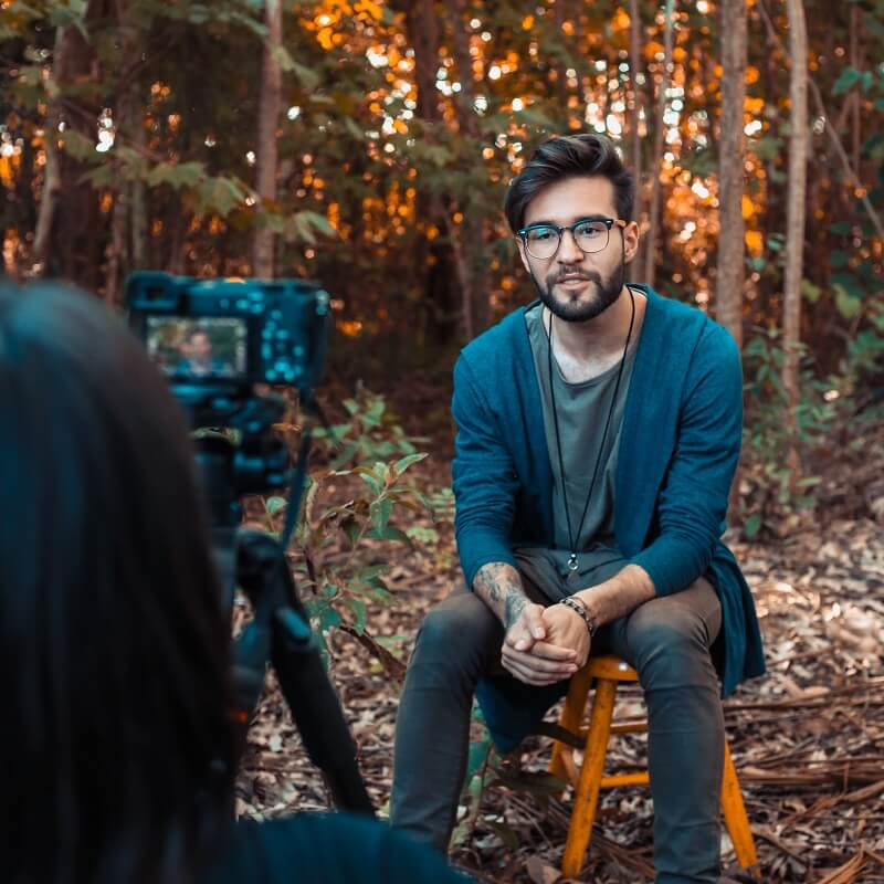 A young man sitting on a chair in the forest being filmed by the camera